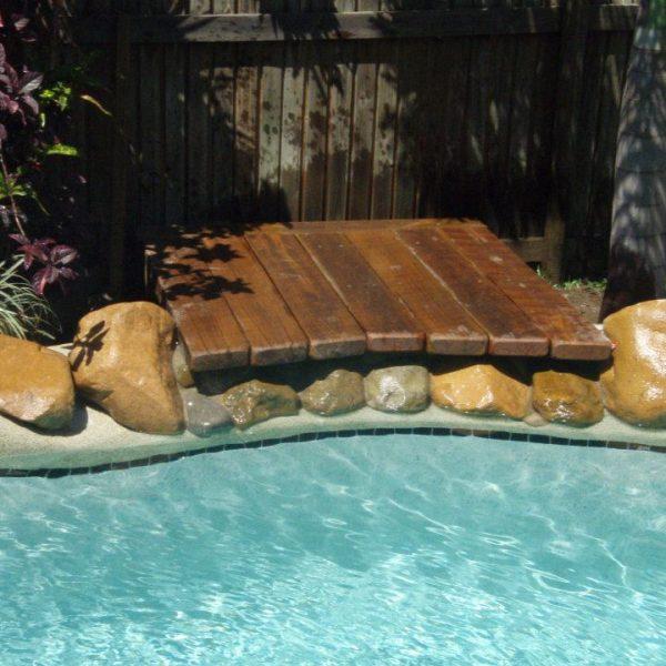 Freeform pool with wooden bridge